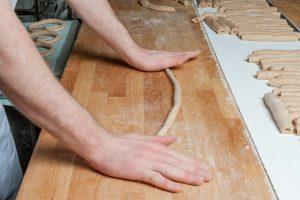 Dinkelbretzeln werden (beinahe im Sekundentakt) von Hand gedreht