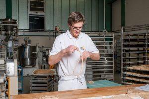 Hier wird eines der badischen Grundnahrungsmittel von Hand gedreht: Bretzelproduktion